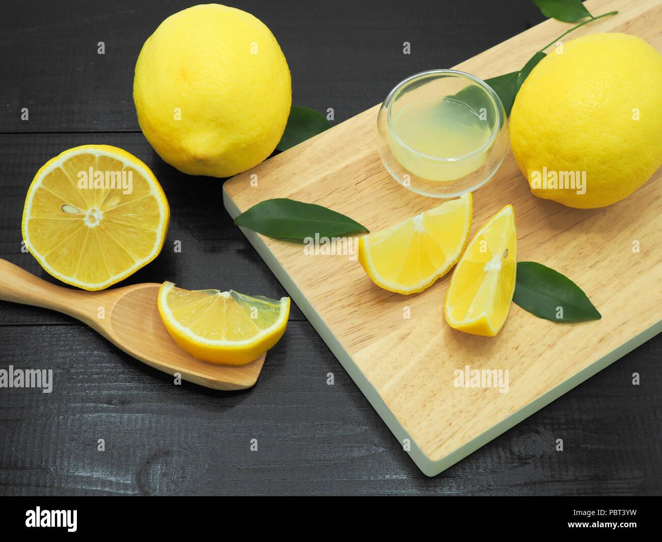 fresh lemon juice in small bowl and lemon slice on dark wood