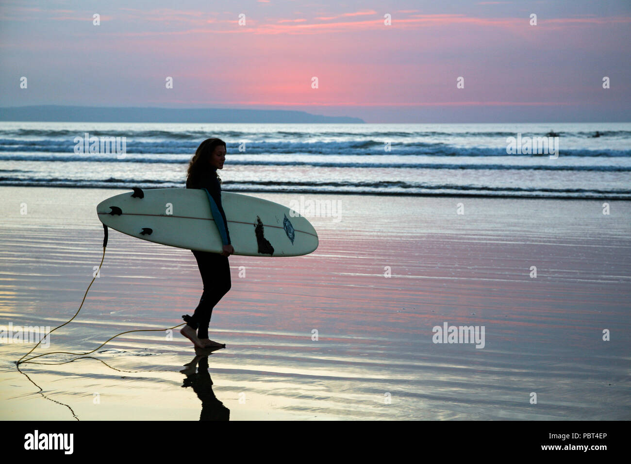Young female surfer carrying her surfboard as she heads off in to the sea to catch a wave surfing at Westward Ho! beach, North Devon, England, Europe. Stock Photo