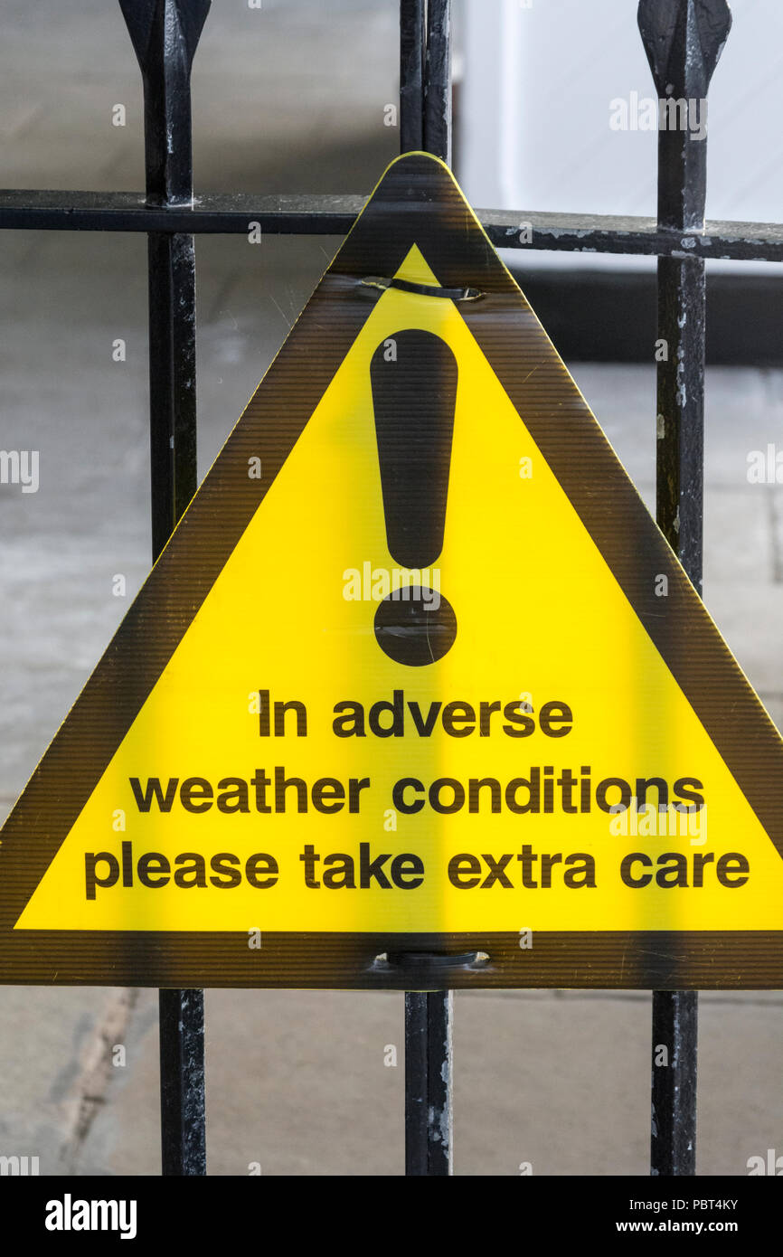 Yellow warning sign - warning of hazardous snow and wet conditions in a public space. - Stock Image