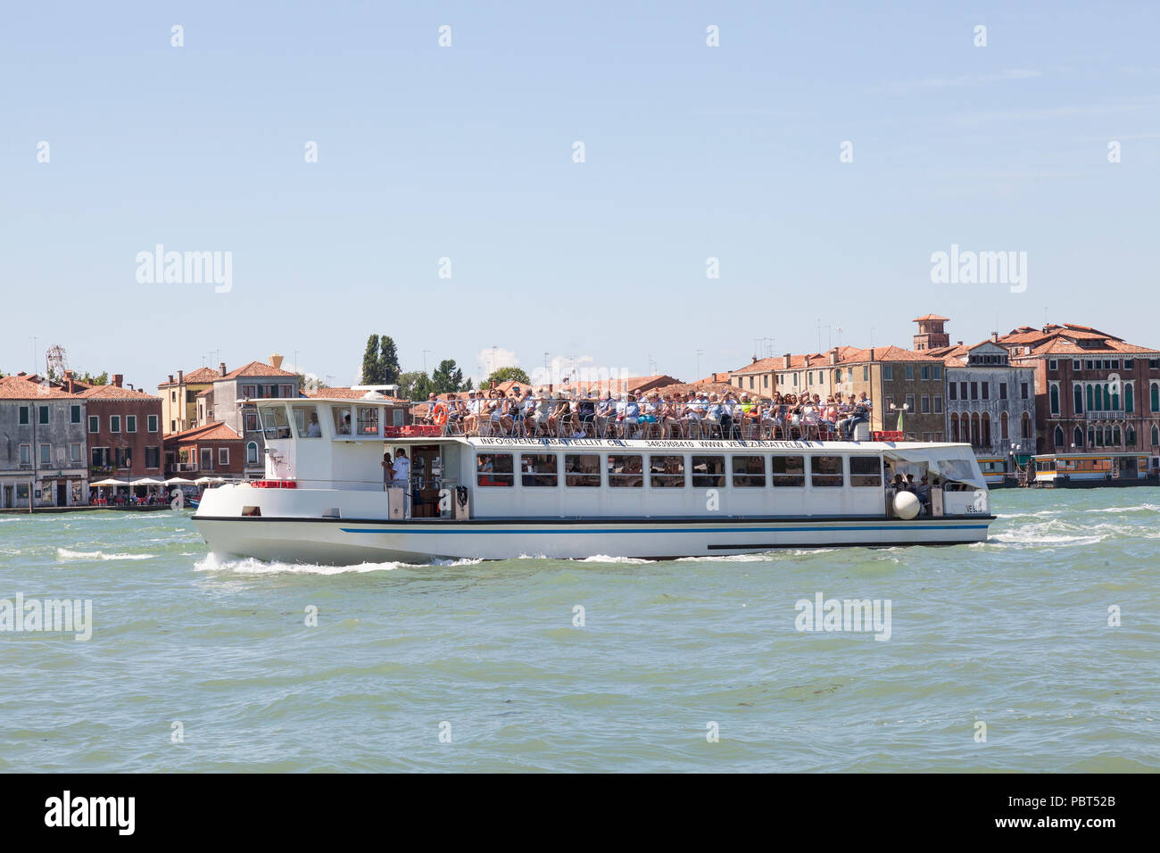 Large tour group on the upper deck of a tour boat sightseeing on the  Giudecca Canal, Venice, Veneto, Italy. Stock Photo