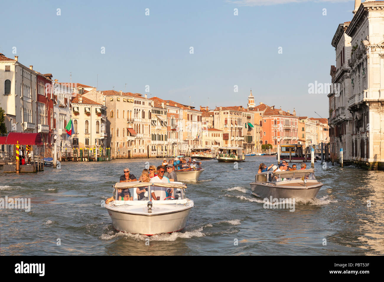 Water taxis with tour groups on the Grand Canal at sunset, Venice, Veneto, Italy passing the historic palazzos, palaces of Cannaregio. Busy water traf - Stock Image