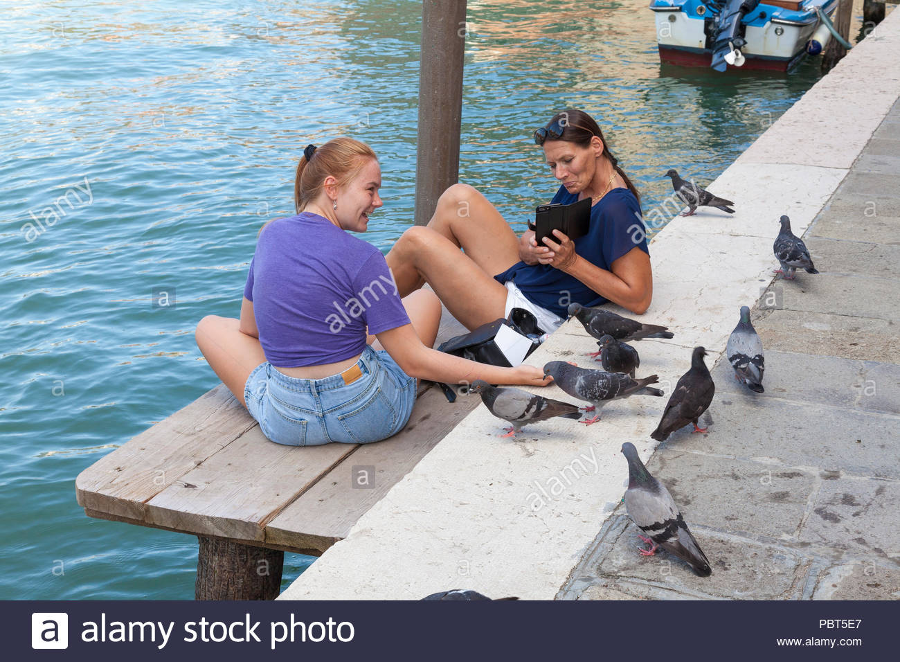 Two happy ladies relaxing feeding pigeons by hand on  a canal, Murano, Venice, Italy sitting on a wooden deck in the shade to escape the heat wave. - Stock Image