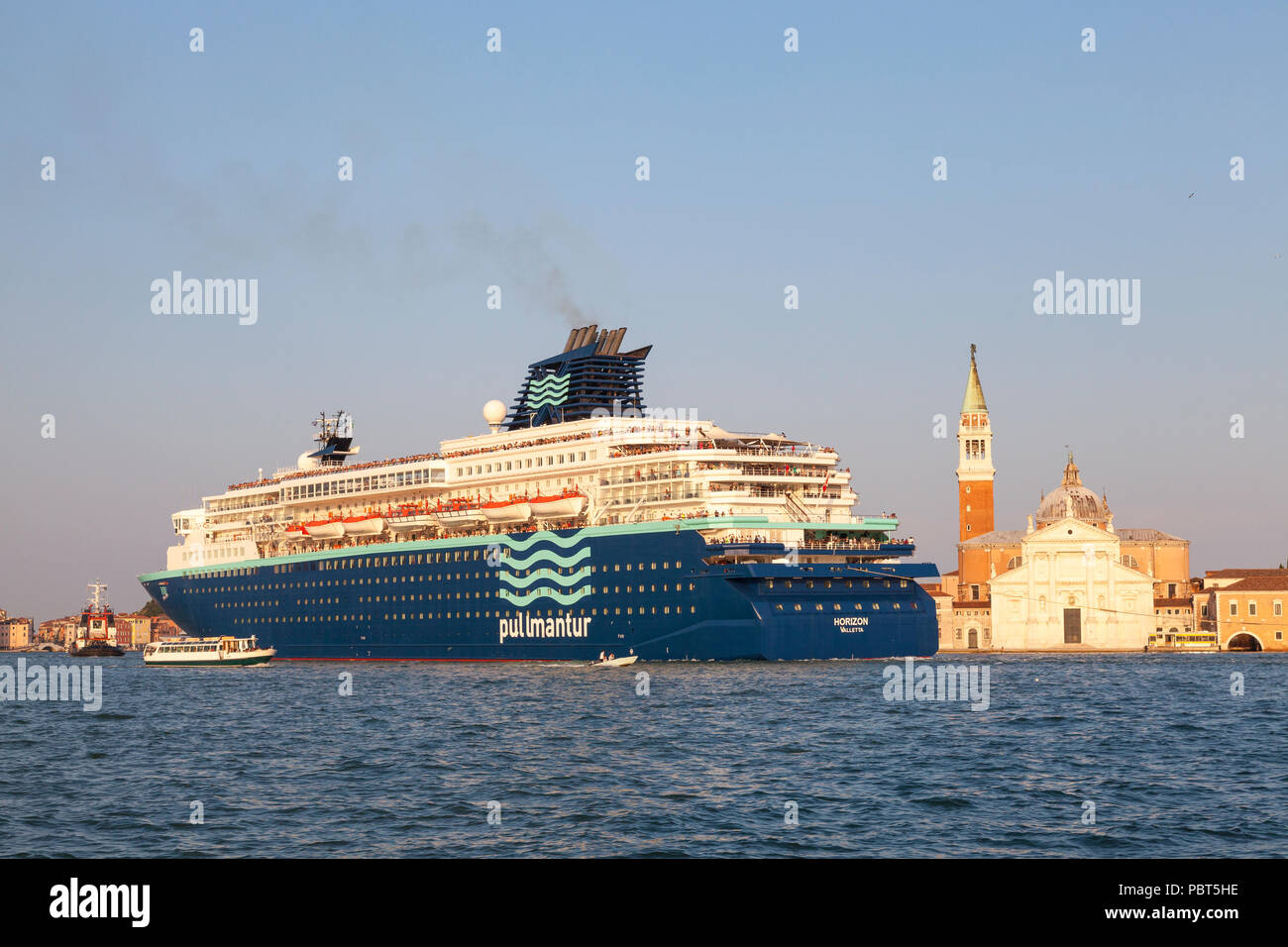 Pullmantur Horizon cruise liner passing  San Giorgio Maggiore, Giudecca Canal, St Marks Basin,  under tow, Venice, Veneto, Italy on departure at sunse - Stock Image