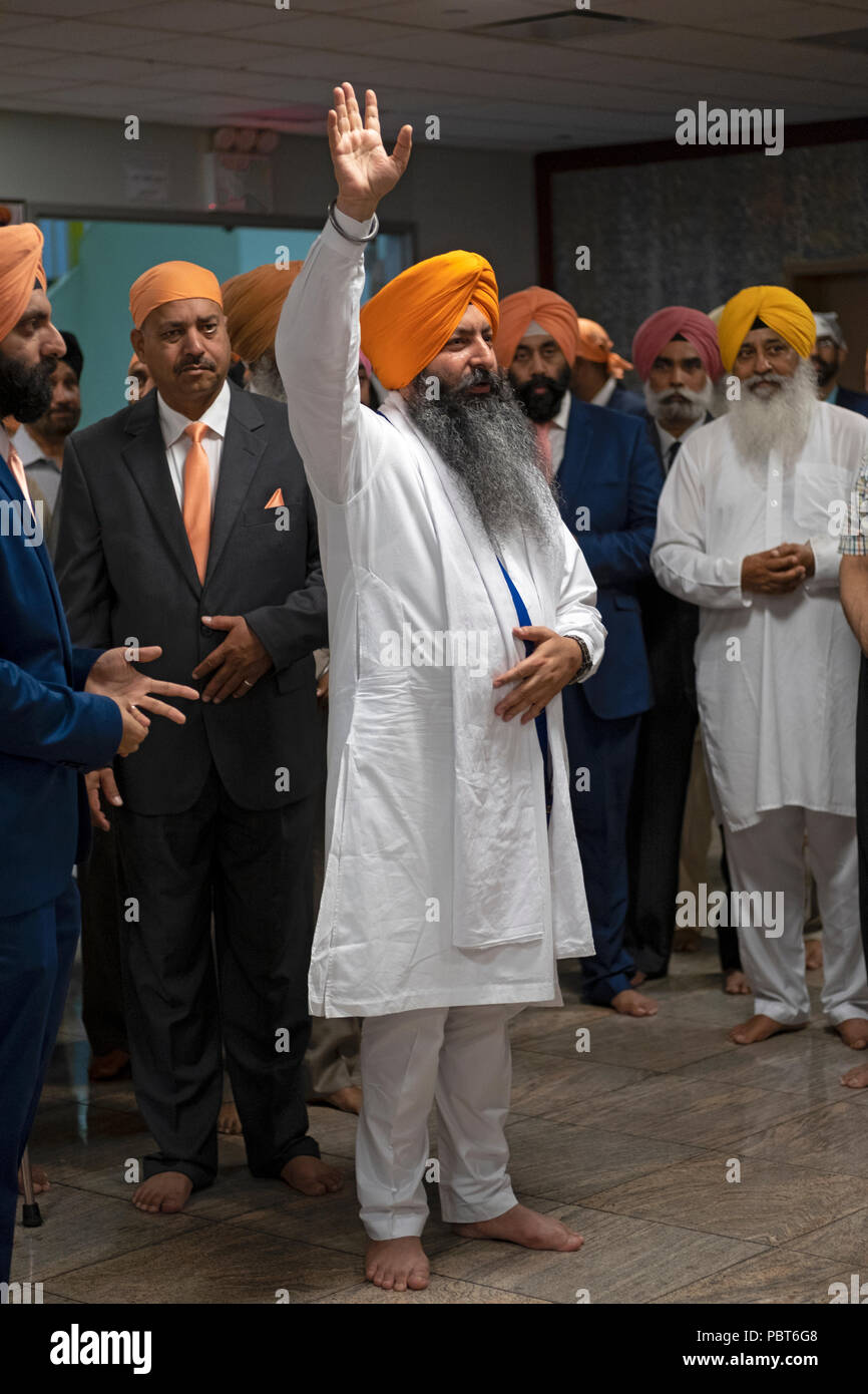 A priest blesses the groom and family prior to his wedding at the Sikh Cultural Center in Richmond Hill, Queens, New York. - Stock Image