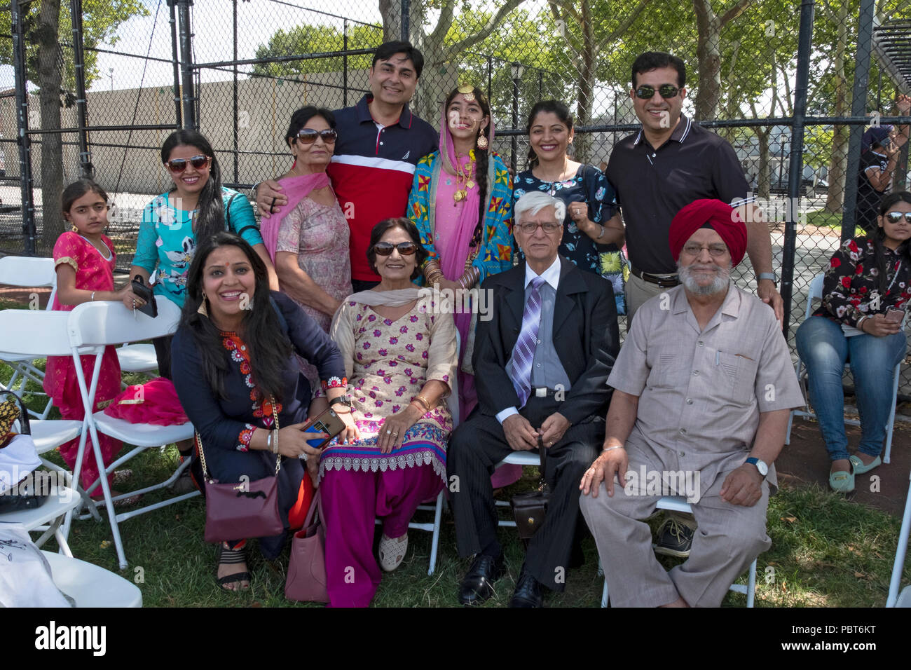 A posed portrait of an extended family at Sikh Gurmat Games at Smokey Park in Queens, New York. The girl in the back row won a fashion contest. - Stock Image