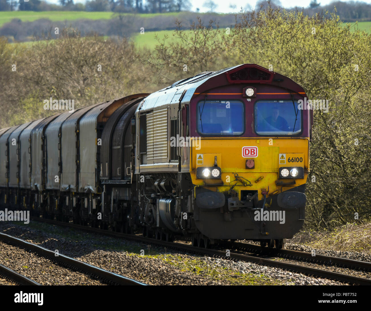 Heavy diesel electric rail freight locomotive hauling a train of wagons - Stock Image