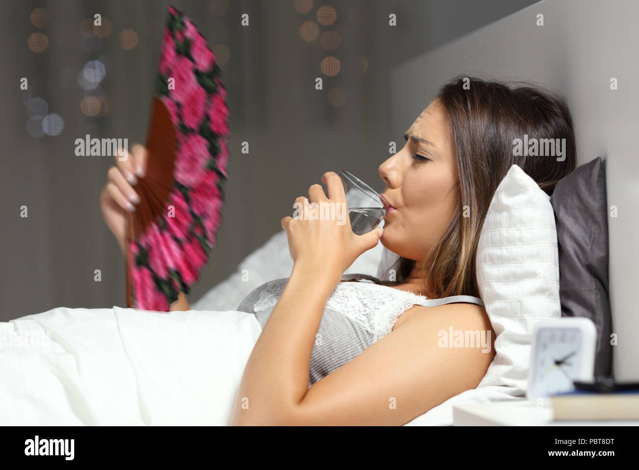 Girl suffering a heat wave drinking water and fanning on a bed in the night at home Stock Photo