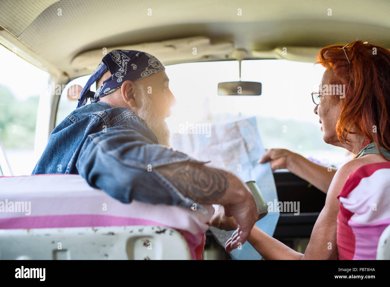 A hipster senior couple on vacation in a van, looking at a ma - Stock Image