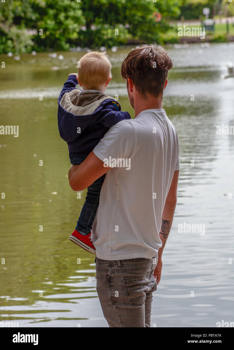 Father holding his toddler son at a lake - Stock Image