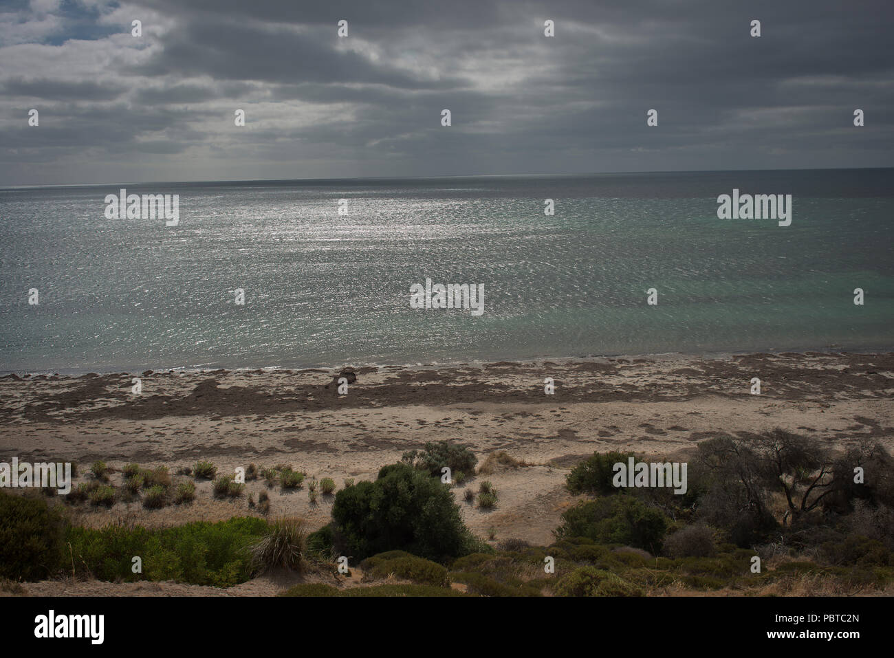Sea view and reflections with remote bush land - Stock Image