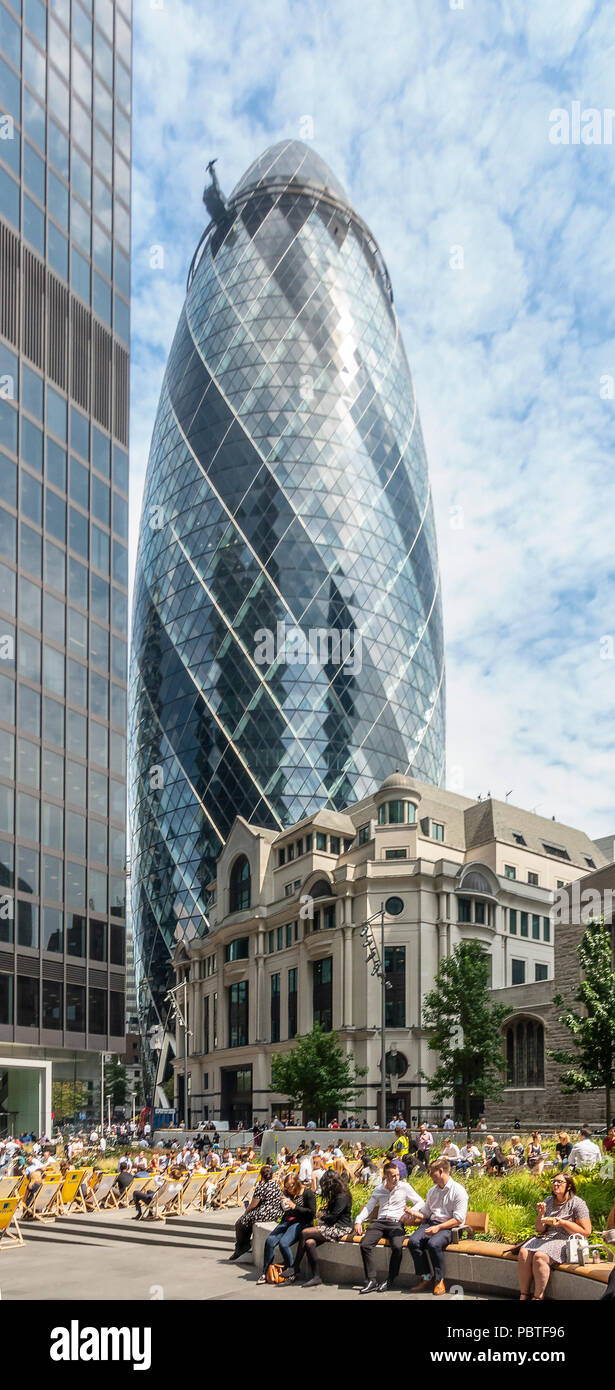 The Gherkin / 30 St Mary Axe, and St Helen's tower above Fitzwilliam House and local workers and visitors relaxing in St Helen's Square. - Stock Image