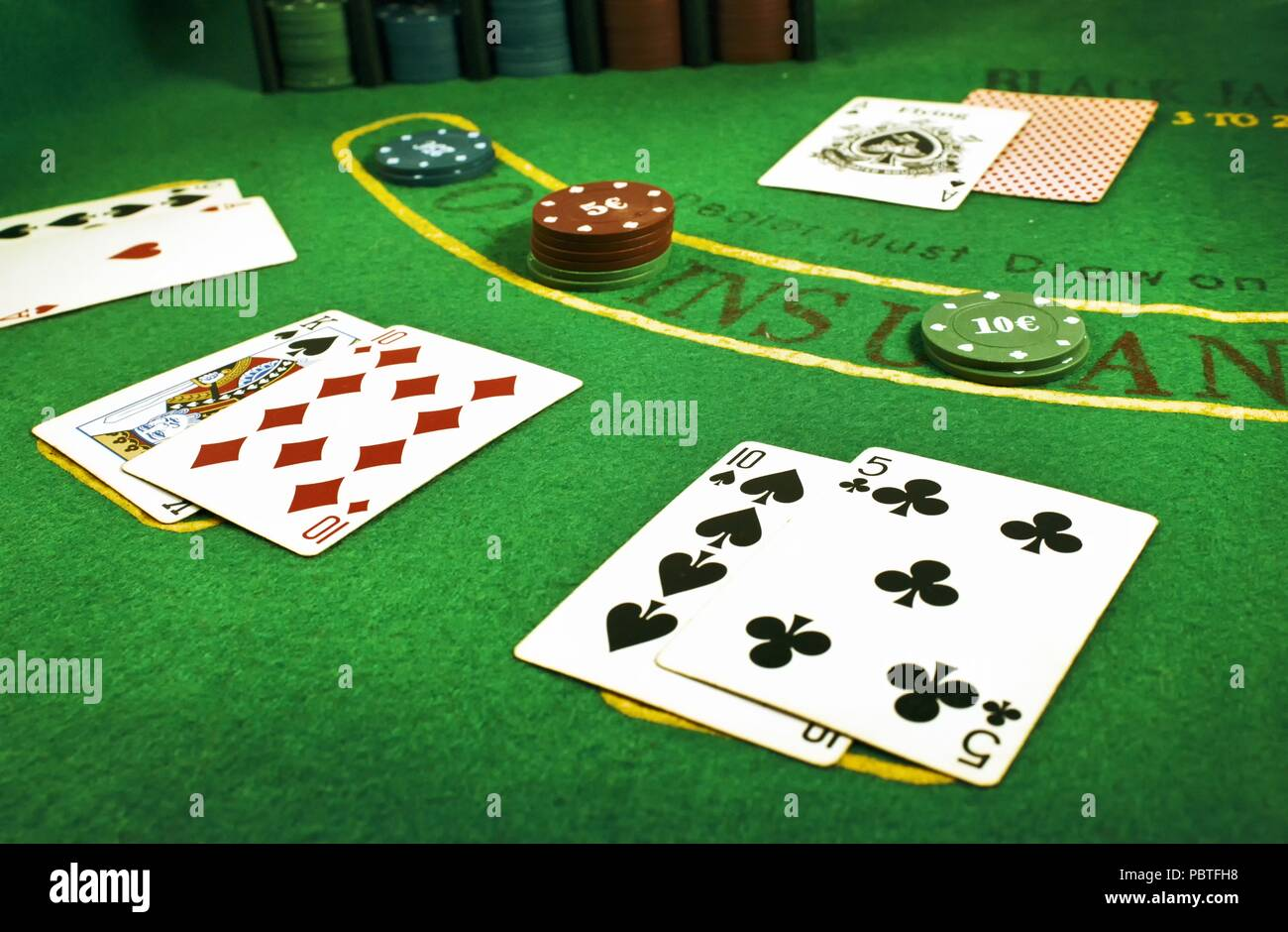 Closeup of dealt cards and stacks of chips on a Blackjack table in a casino - Stock Image