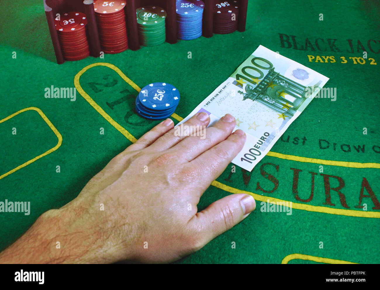 100 Euro note being exchanged for gaming chips on a green felt Blackjack table at the casino - Stock Image