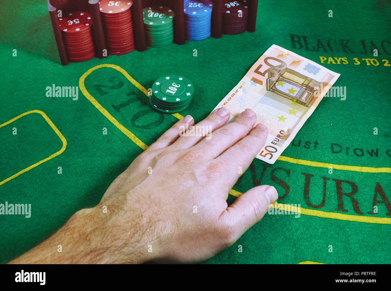 50 Euro note being exchanged for gaming chips on a green felt Blackjack table at the casino - Stock Image