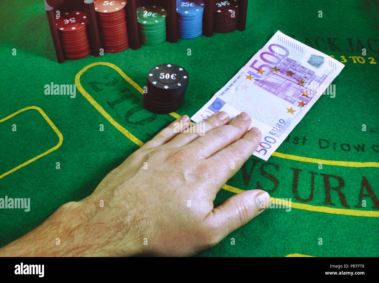 500 Euro note being exchanged for gaming chips on a green felt Blackjack table at the casino - Stock Image