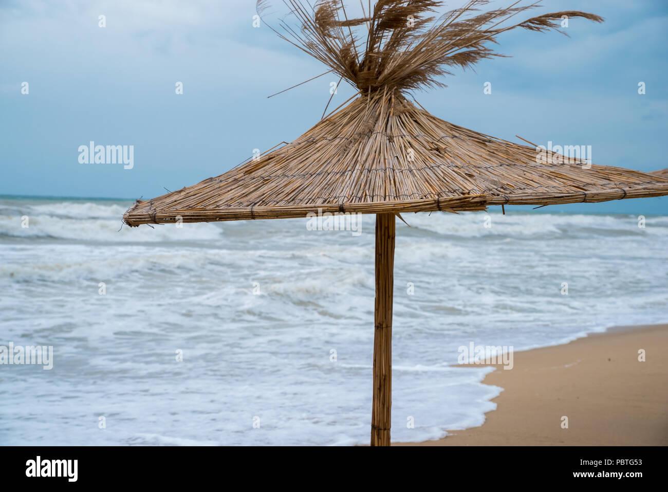 Straw umbrella on the beach. - Stock Image