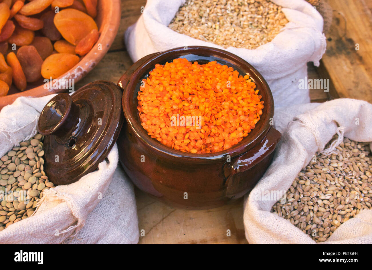 Ceramic clay pot with red lentils and sacks of legumes and grains in a food market stand - Stock Image