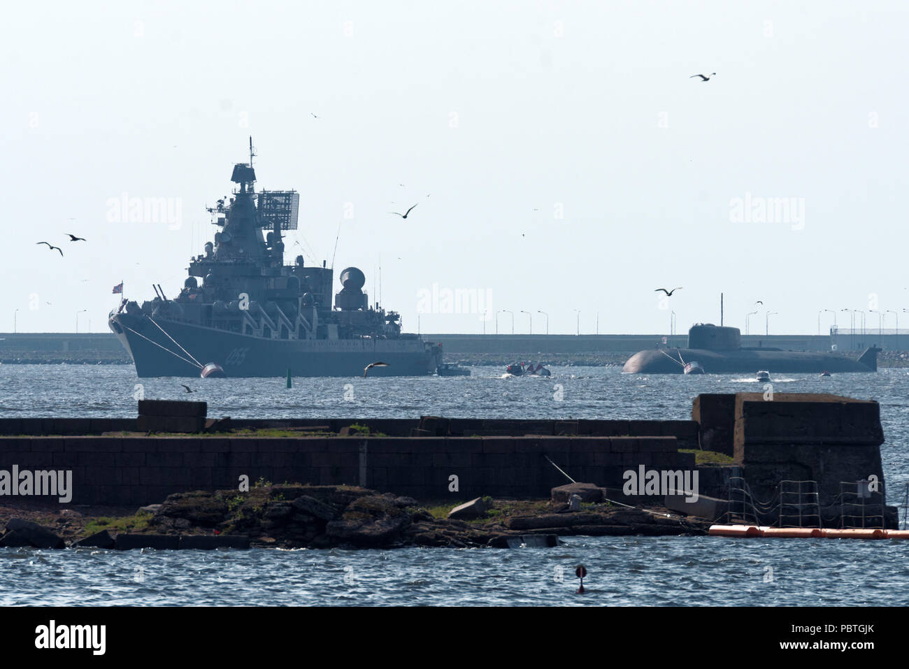 Kronstadt, St. Petersburg, Russia - July 28, 2018: Guided missile cruiser Marshal Ustinov and nuclear-powered submarine Orel anchored in Kronstadt bef - Stock Image