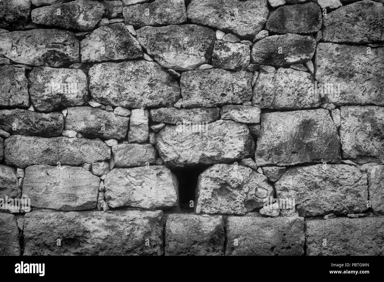 Old rustic stone wall in black and white with varied and sizes and textures - Stock Image