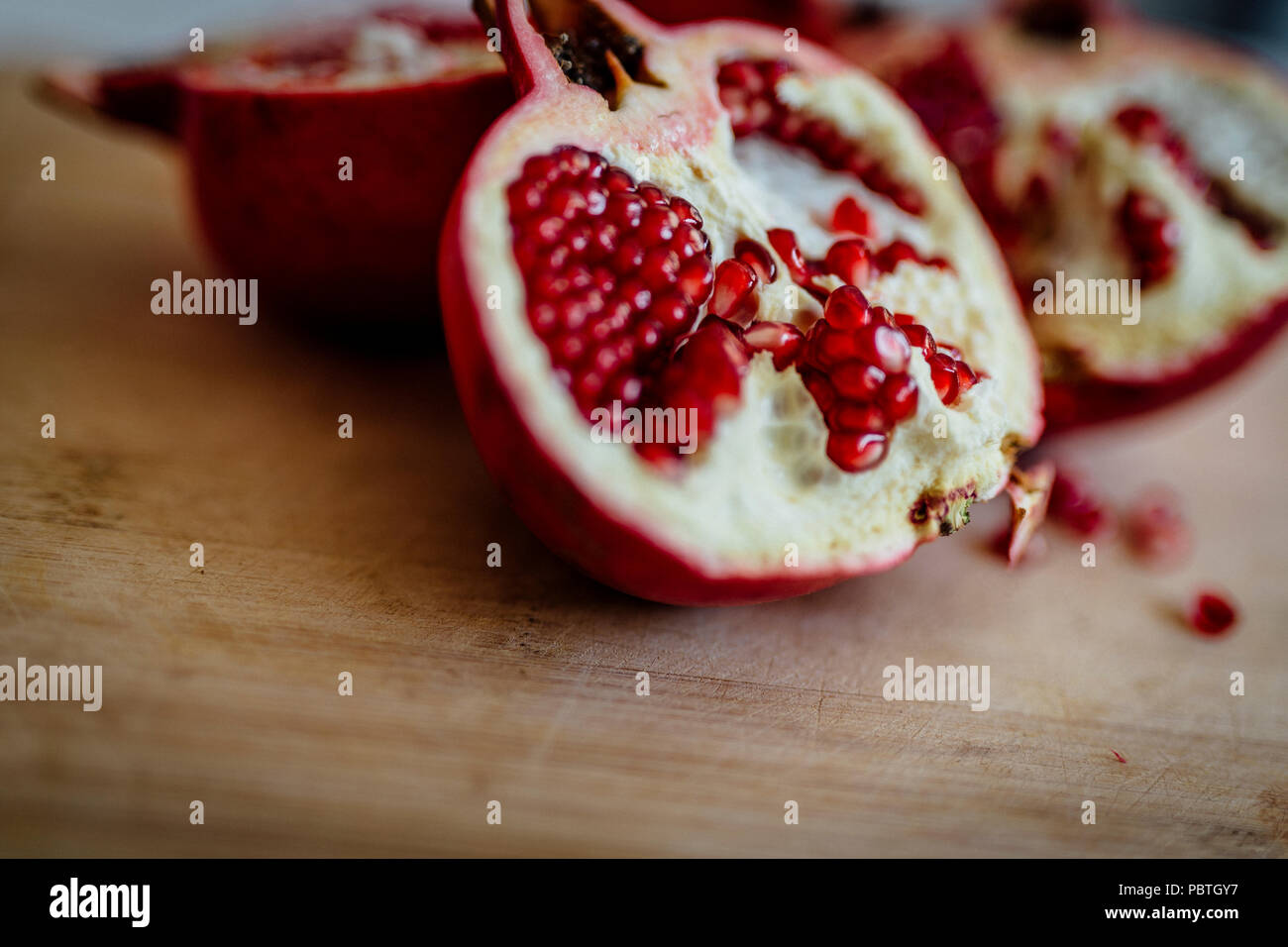 Fresh POMEGRANATE on wooden background. - Stock Image