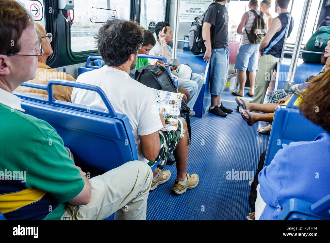 10614574be7 Miami Beach Florida Metrobus bus public transportation passengers seats  mass transit standing sitting man men aisle