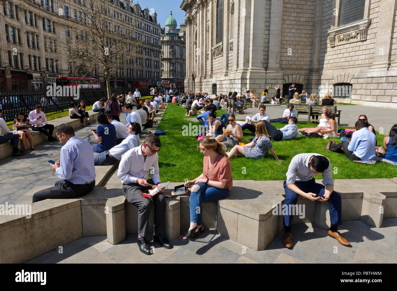 People sitting outside St Paul's Cathedral and enjoying the hot weather, City of London, England, United Kingdom - Stock Image