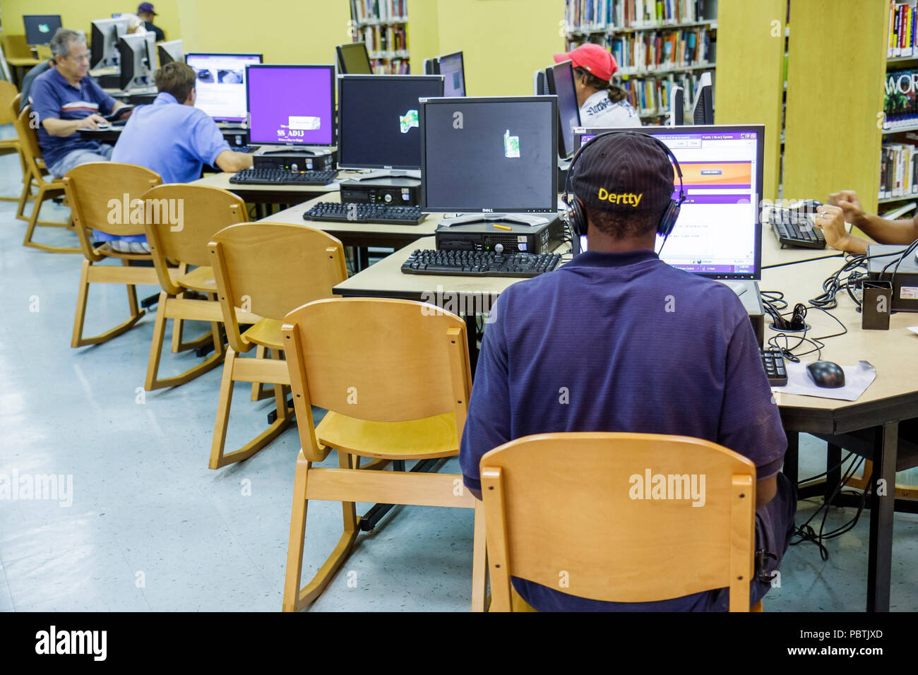 Miami Beach Florida South Shore Public Library desks computers chairs monitors Internet access free patrons - Stock Image