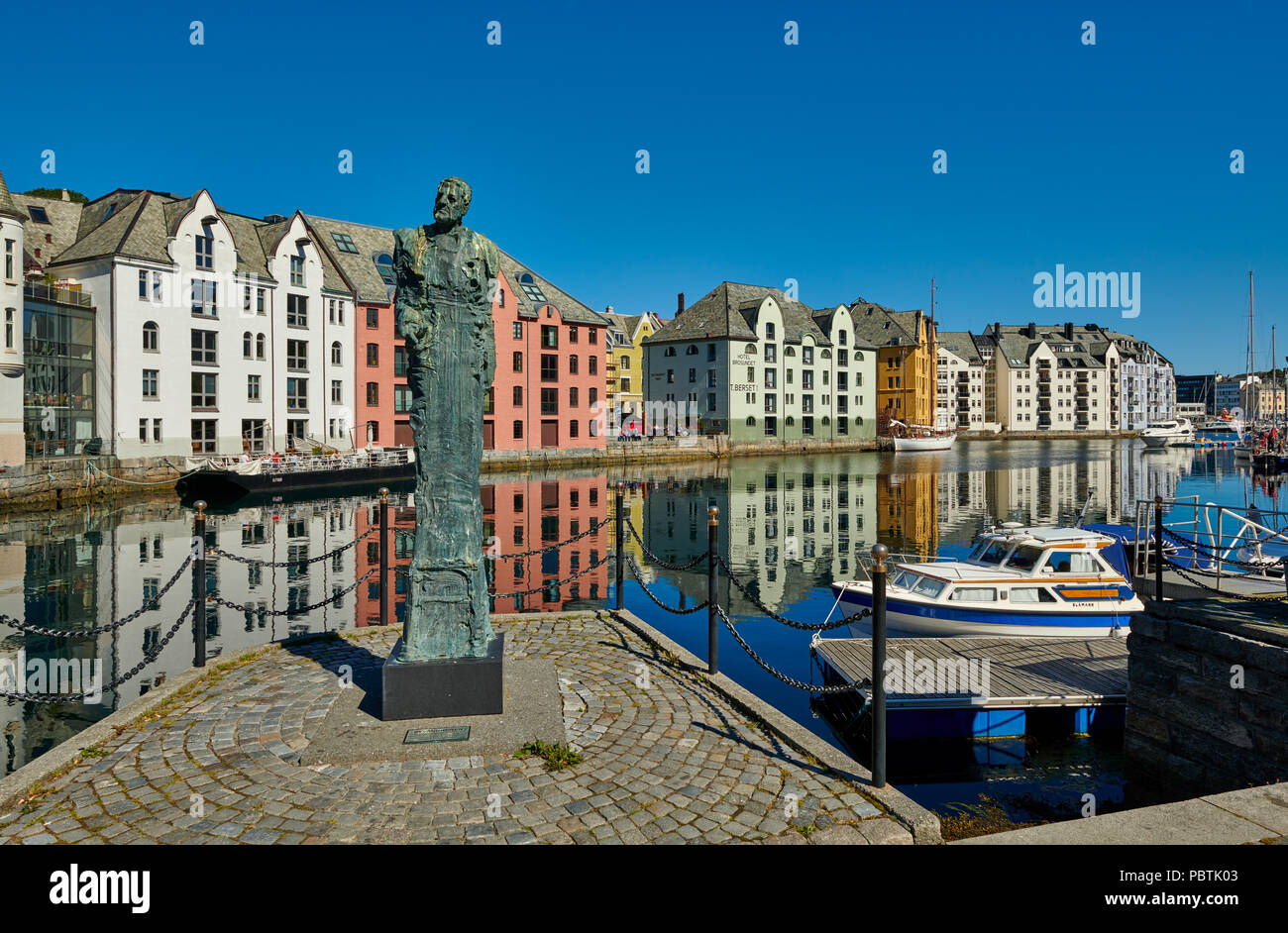 statue in front of view of old harbor with historical Art Nouveau buildings, Ålesund, Norway, Europe - Stock Image