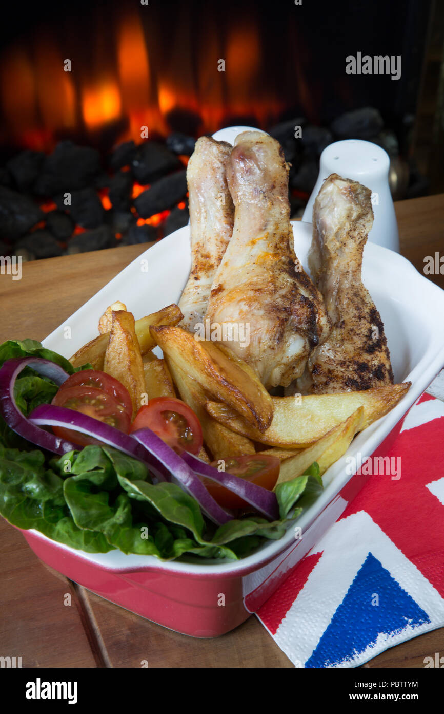 English pub meal of Roast Chicken drumsticks with chips/fries and a fresh mixed salad - Stock Image
