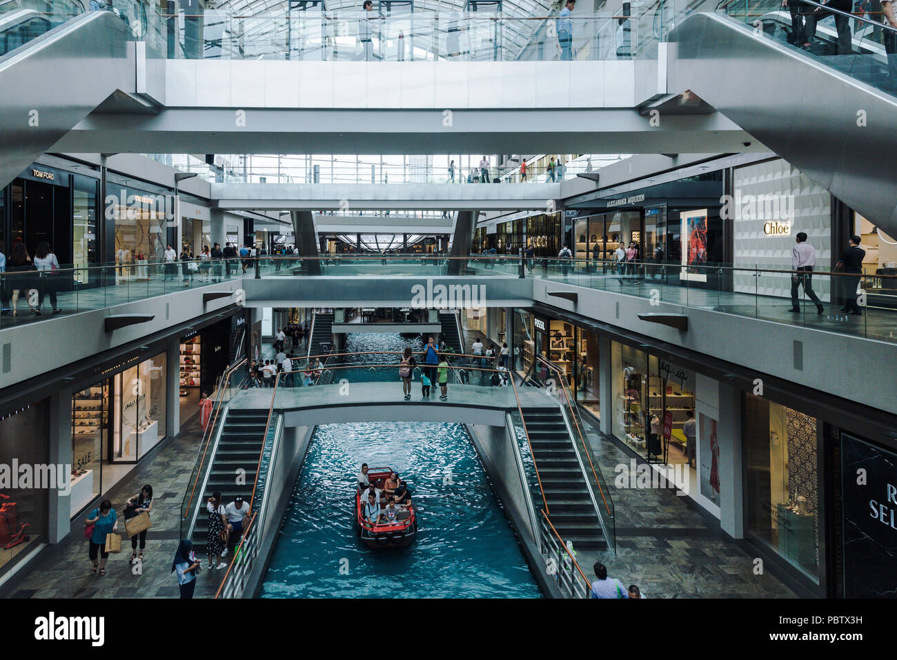 Tourists boat in luxury mall canal in the shoppes at marina bay sands. Singapore - Stock Image