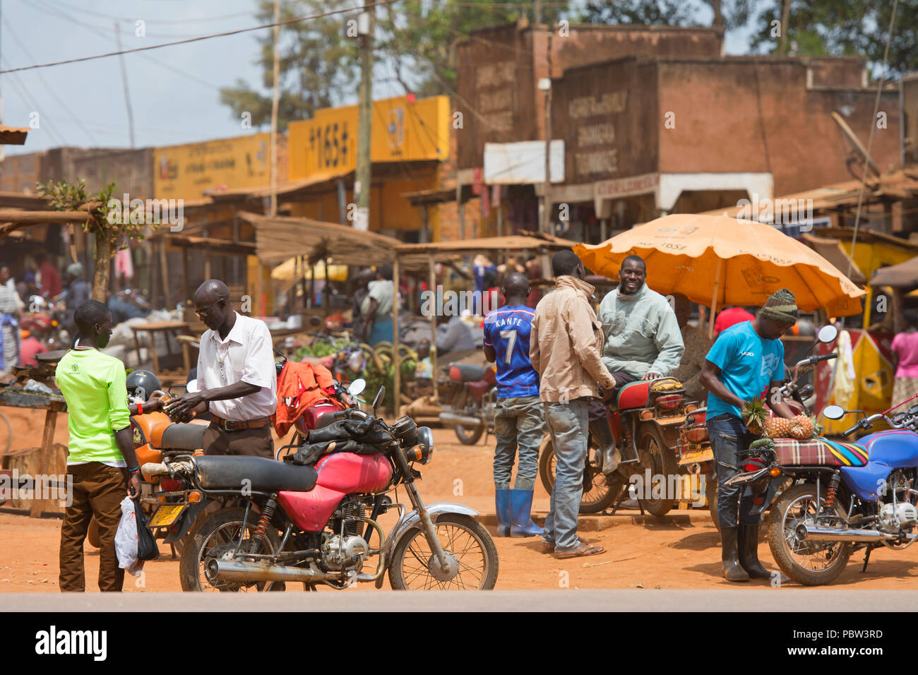 Small Town, Street Scene, Men with Motorcycles, Crowded Busy Market, Transport, East Africa, Uganda - Stock Image