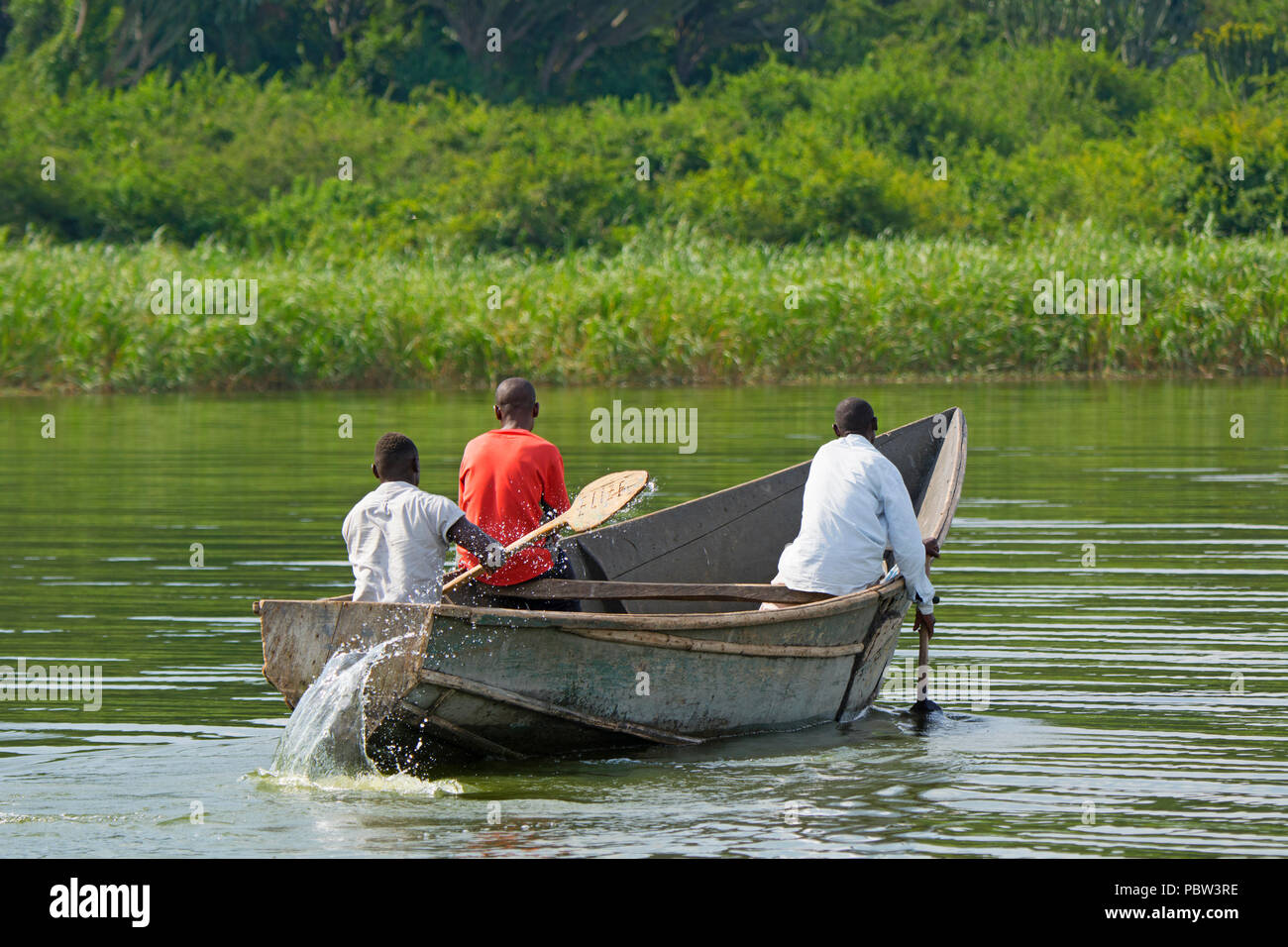 Three Men in a Boat, Fishermen Rowing, Paddling along the Kazinga Channel, Uganda, East Africa - Stock Image