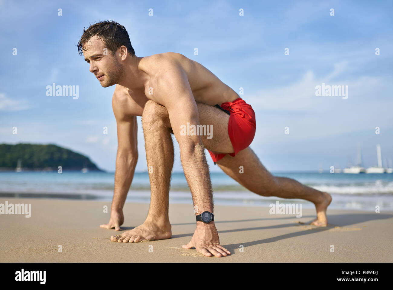 Handsome tanned man on the sand beach on the sunny background of the sea with white boats and the blue sky. He wears a red swim trunks and a dark watc - Stock Image