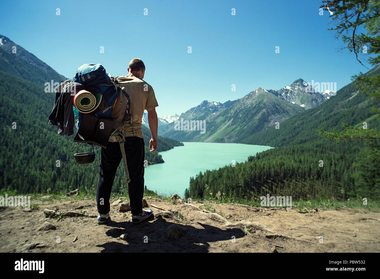 f3484912df23 Man Traveler with big backpack mountaineering Travel Lifestyle concept lake  and mountains on background Summer extreme vacations outdoor. Altai mounta