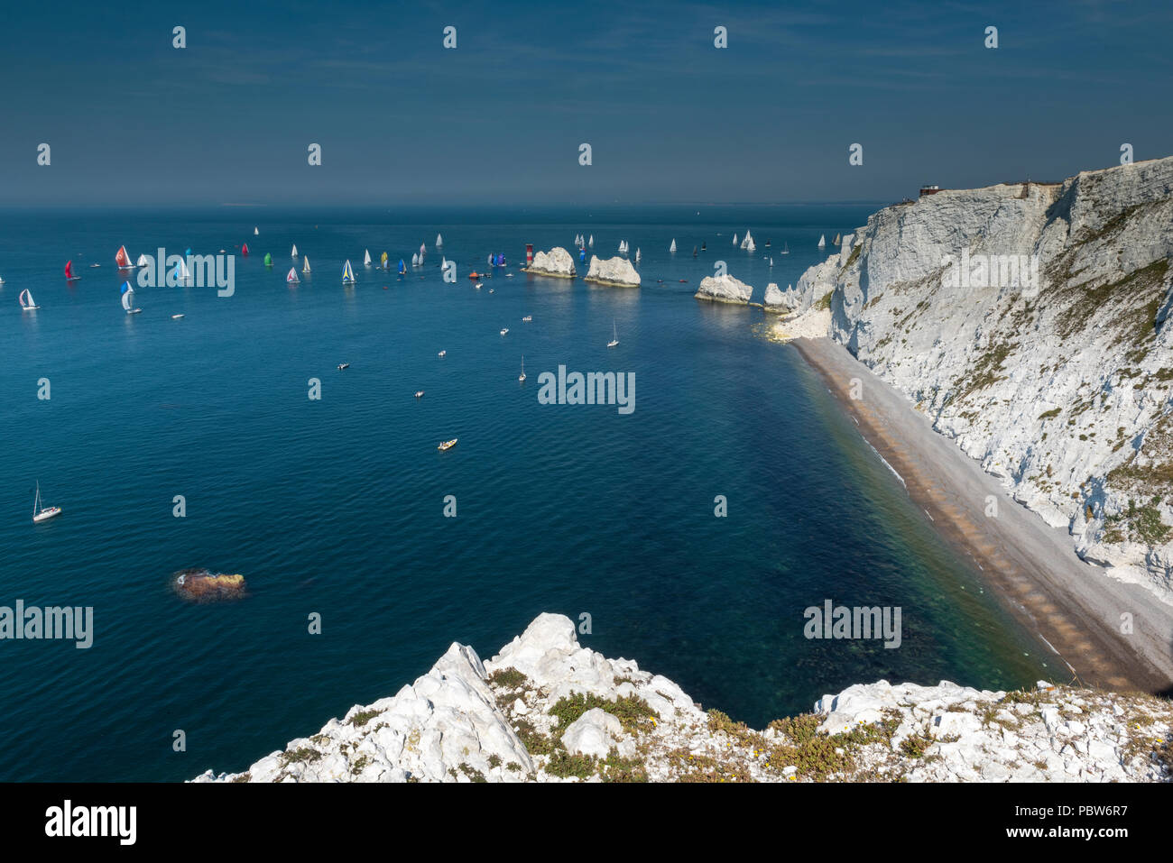 the round the island yacht race passing the needles and cliffs on the isle of wight.on a hot summers day. - Stock Image