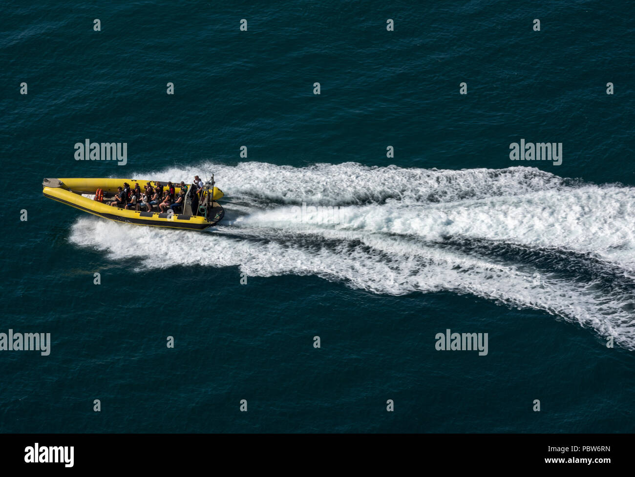 a high speed fast rib boat racing across the water full of passengers causing waves and wake. - Stock Image