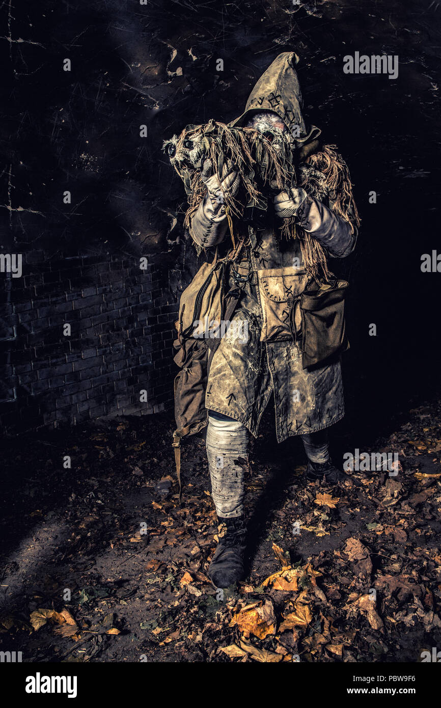 Post apocalyptic creature in gas mask armed gun - Stock Image