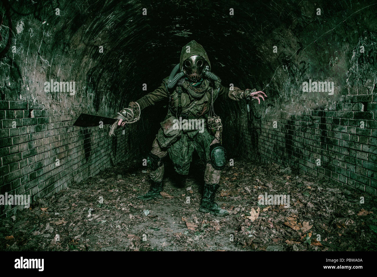 Post apocalyptic underground creature in gas mask - Stock Image