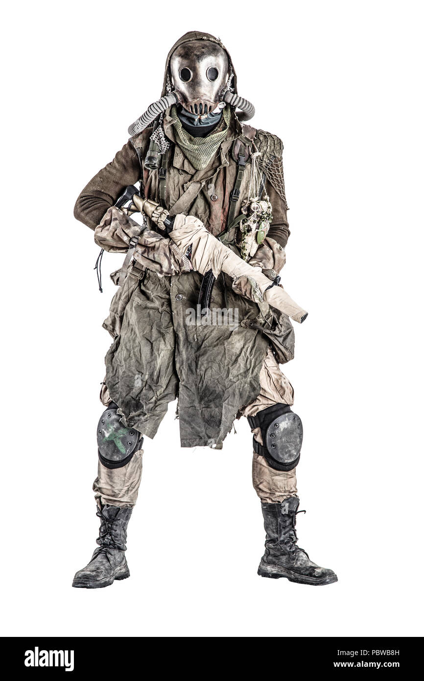 Post apocalyptic creature in gas mask armed by gun - Stock Image