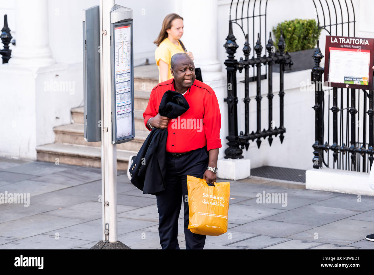 London, UK - June 22, 2018: Neighborhood district of South Kensington man carrying Sainsbury's grocery shopping bags waiting to cross street, bus stop - Stock Image