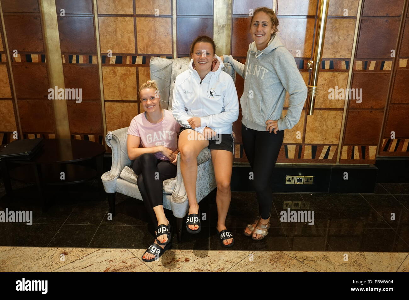 30.07.2018, Great Britain, London: Hockey, World Cup, Field, Ladies. The hockey players (l-r) goalkeeper Julia Ciupka, Charlotte Stapenhorst, Marie Mävers from Germany sit in the London team hotel Grange City. The German women's hockey team will once again face Spain in the quarter-finals of the World Cup in London. The Olympic bronze medallist Germany had previously secured first place in preliminary round group C with three wins and was thus directly qualified for the round of the best eight. Photo: Nina Niedermeyer/dpa - Stock Image
