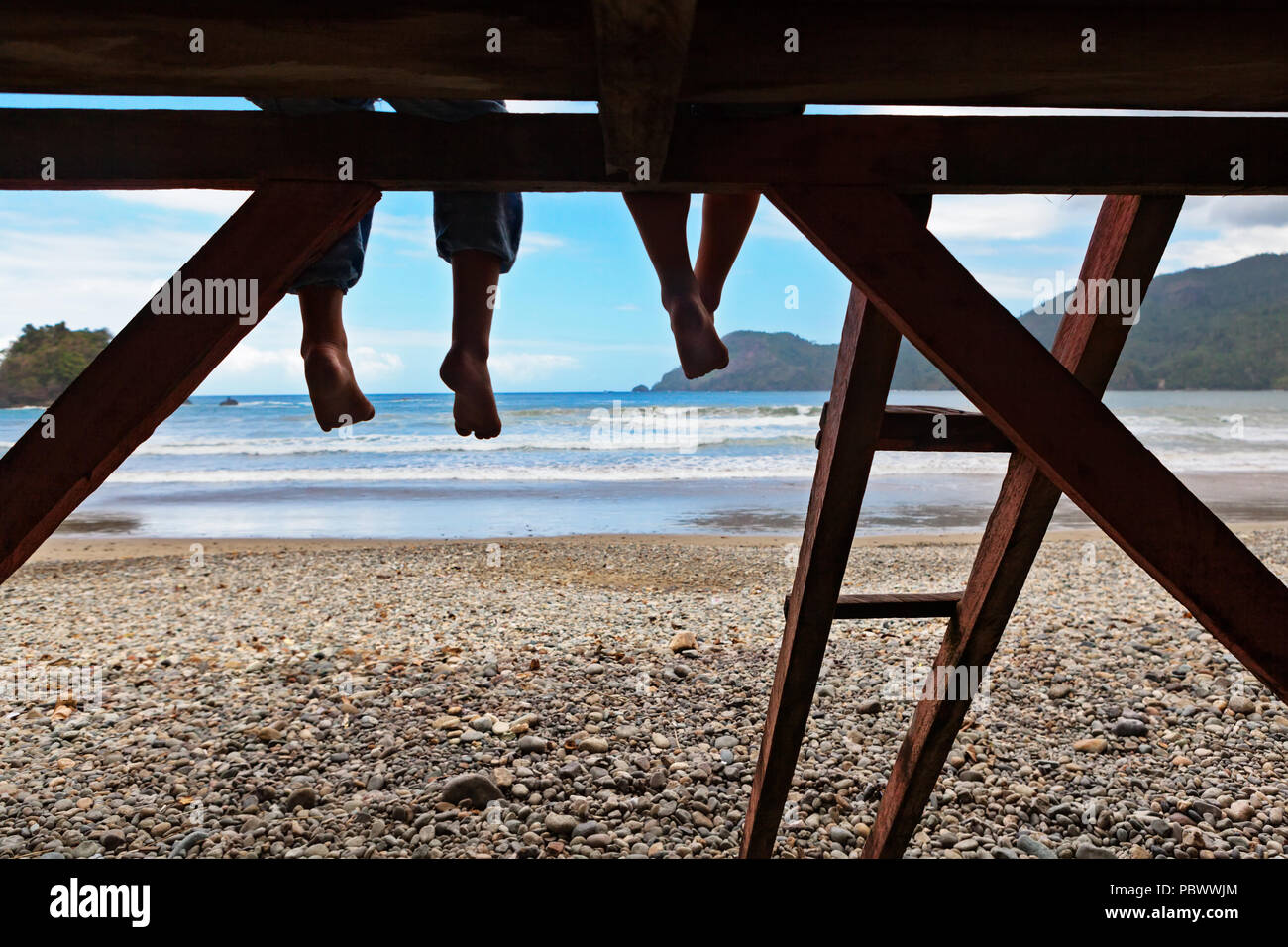Happy kids have fun on beach walk. Children sit on lifeguard tower edge, dangling bare feet, look at sea surf. Black silhouette. Vacations travel life - Stock Image