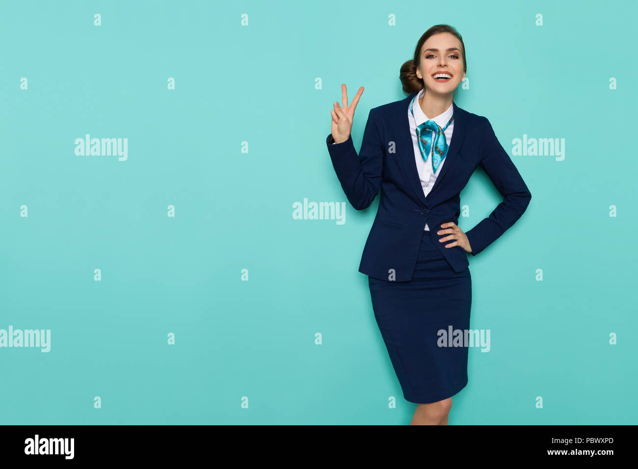 Smiling stewardess in blue formal wear is showing peace hand sign and looking at camera. Three quarter length studio shot on turquoise background. - Stock Image