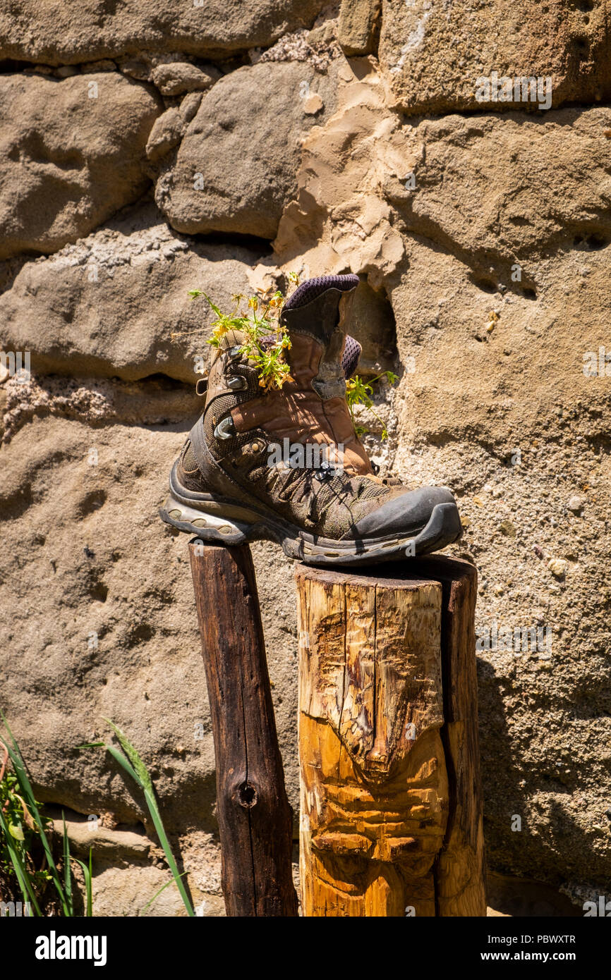 Well worn old walking boot on a post by a stone wall with weeds growing out of it in the Garrotxa volcanic zone, Catalonia, Spain - Stock Image