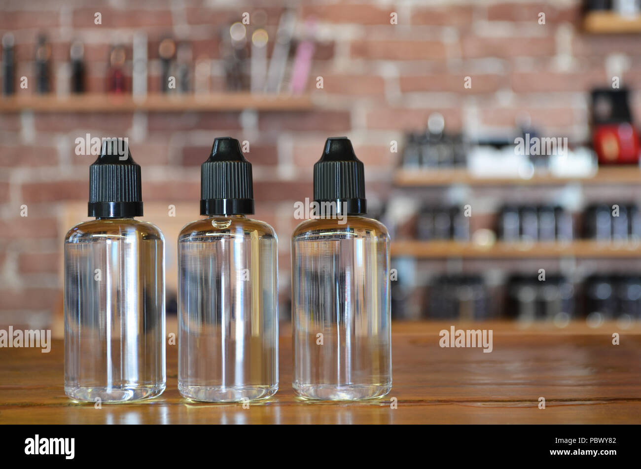 Vape juice bottle on a background of vape shop. E-cigarette for vaping. Popular vape devices - Stock Image