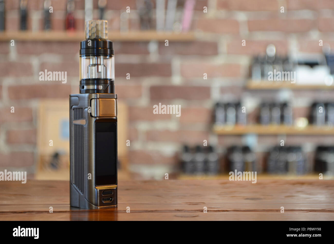 Electronic cigarette with ejuice bottle on a background of vape shop. E-cigarette for vaping. Popular vape devices - Stock Image