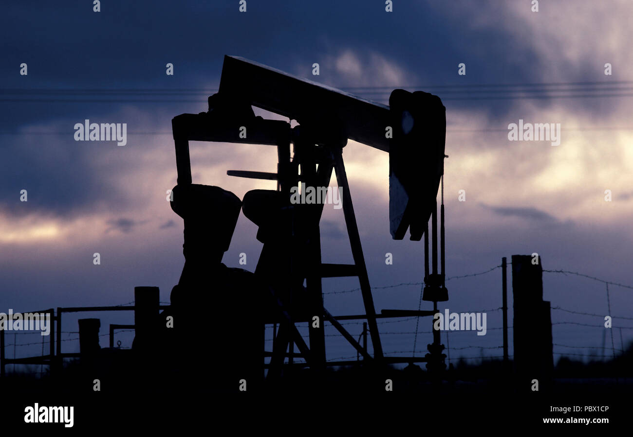 a Texas oil pumpjack working in fading dramatic light - Stock Image