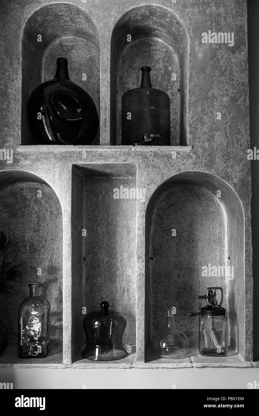 Alcoves containing glass bottles and kitchen utensils in the hotel Cal Sastre, Santa Pau, Catalonia Stock Photo