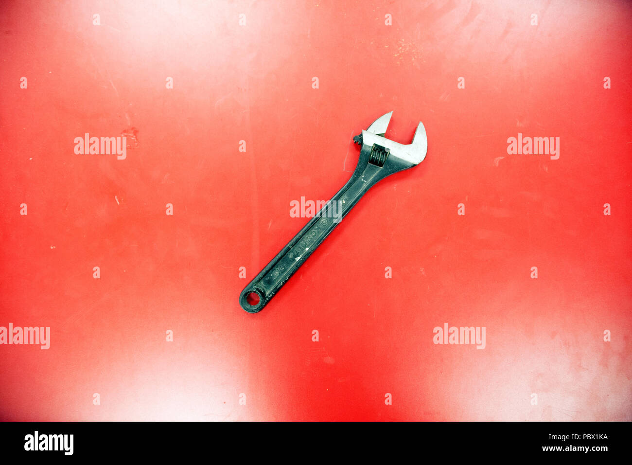 Still life of a crescent wrench alone on the red background - Stock Image