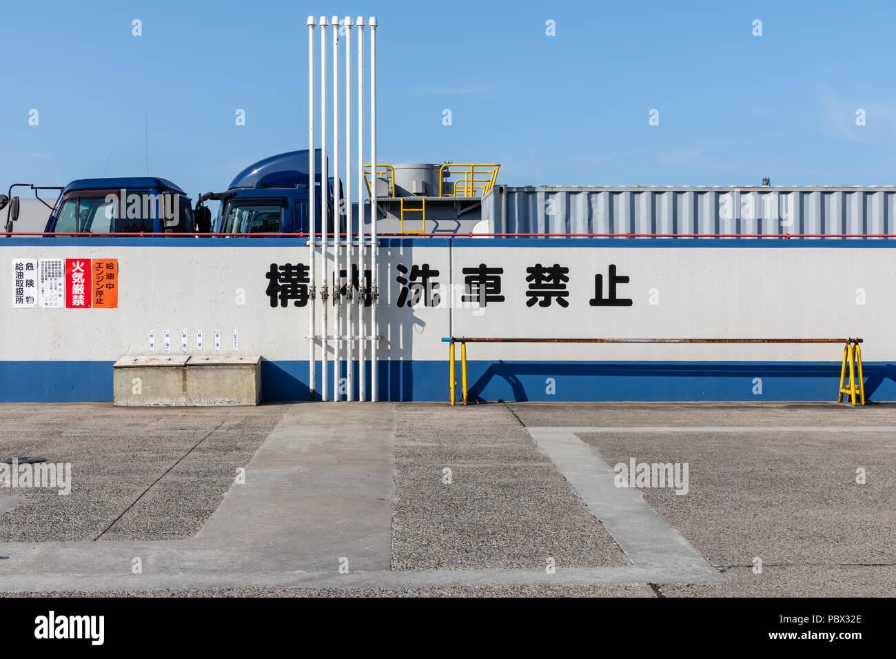 Trucks behind wall with Japanese text; Kawasaki, Kanagawa Prefecture, Japan - Stock Image